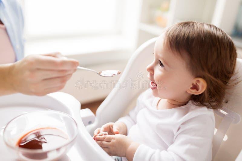 Bambino d'alimentazione della madre con purè a casa immagini stock libere da diritti