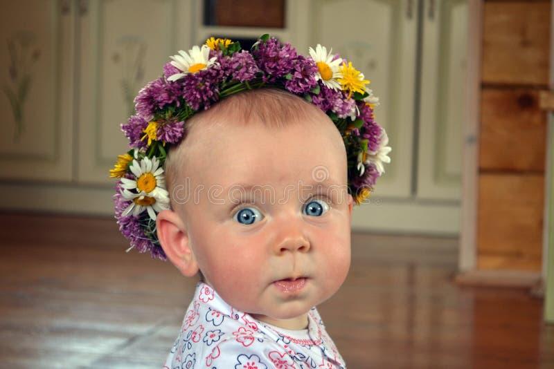 Bambino degli occhi azzurri con la corona dei fiori immagine stock libera da diritti