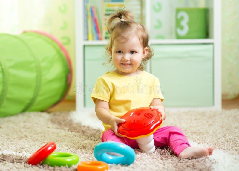 Bambino del bambino che si siede sul pavimento con i giocattoli in stanza dei giochi immagine stock libera da diritti