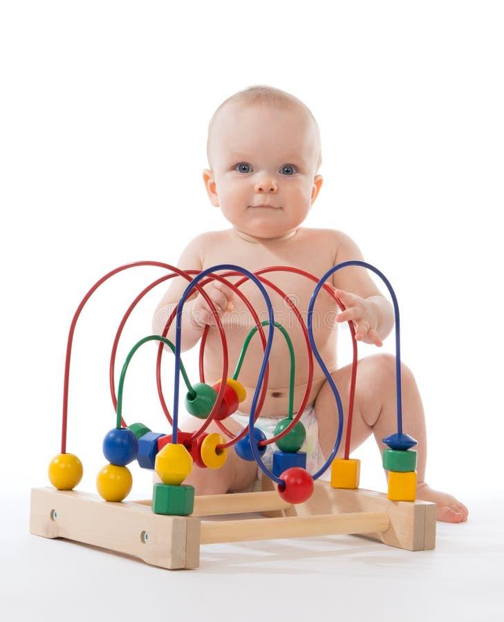 Bambino del bambino del bambino che si siede e che gioca giocattolo educativo di legno fotografia stock libera da diritti