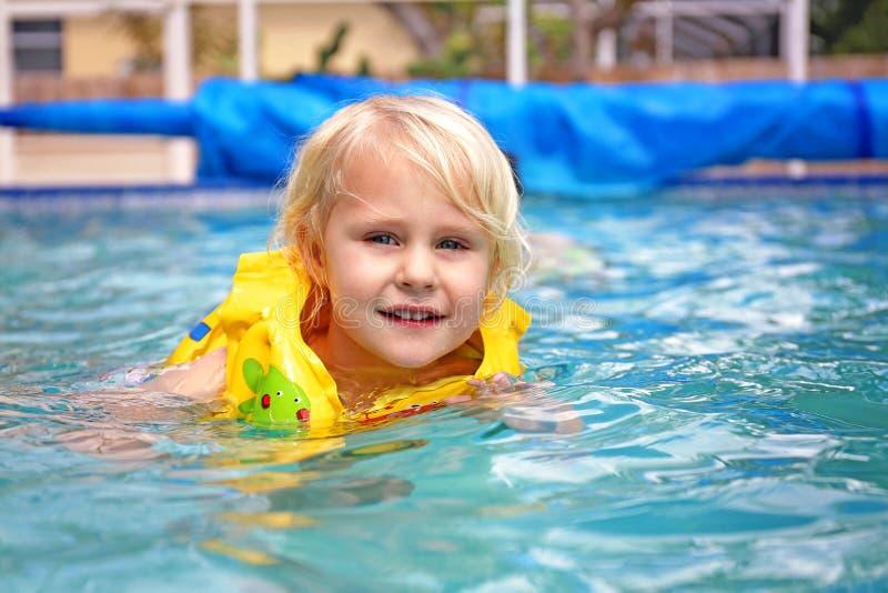 Bambino del bambino che porta il giubbotto di salvataggio gonfiabile che impara nuotare nello stagno della famiglia del cortile immagini stock libere da diritti