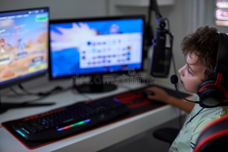 Bambino del nerd che gioca i giochi di computer fotografia stock