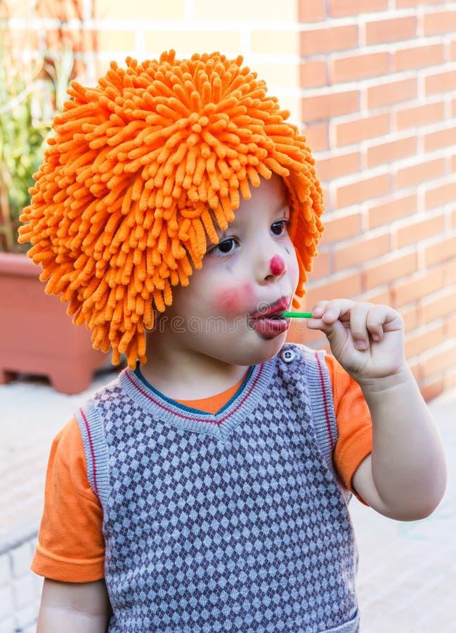 Bambino del pagliaccio che mangia lecca-lecca in un partito fotografie stock libere da diritti