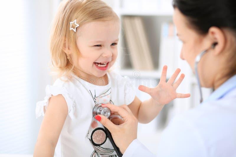 Bambino del paziente e di medico in ospedale La bambina sta esaminanda dal pediatra con lo stetoscopio Ritardi e braccia fotografie stock