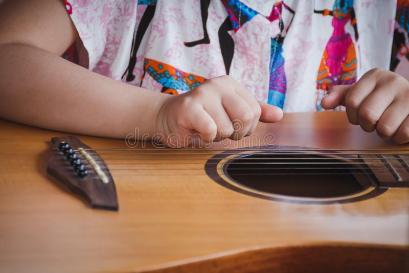 Bambino del primo piano che gioca chitarra Concetto di liftstyle, di apprendimento, dell'hobby, del musicista, del sogno e dell'i immagini stock