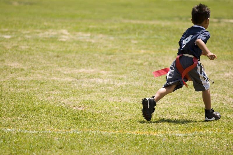 Bambino del ragazzino che gioca calcio di bandiera su un campo aperto fotografie stock