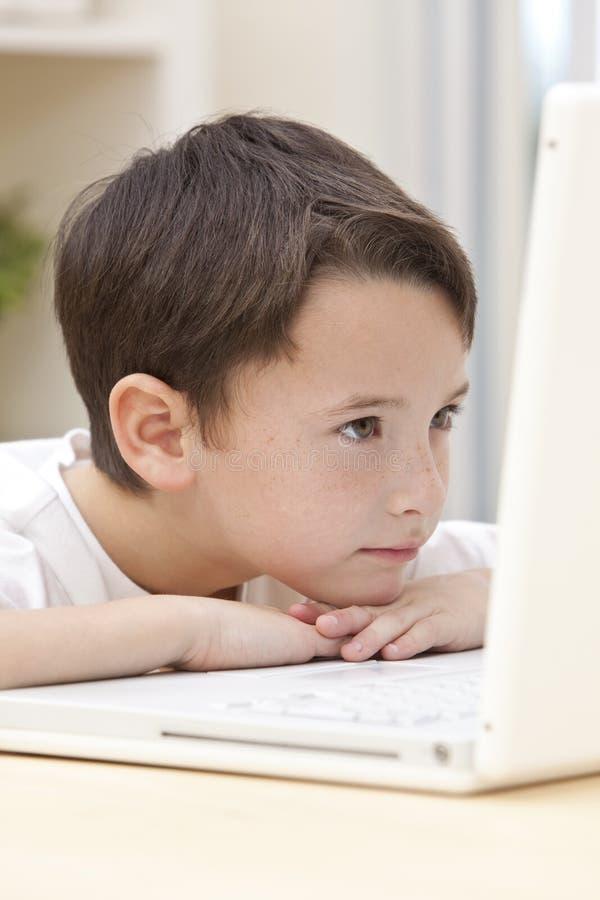 Bambino del ragazzo che per mezzo del computer portatile immagine stock libera da diritti