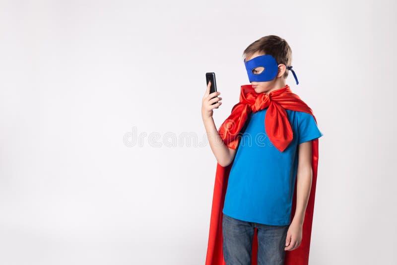 Bambino del supereroe che per mezzo del telefono cellulare fotografia stock libera da diritti