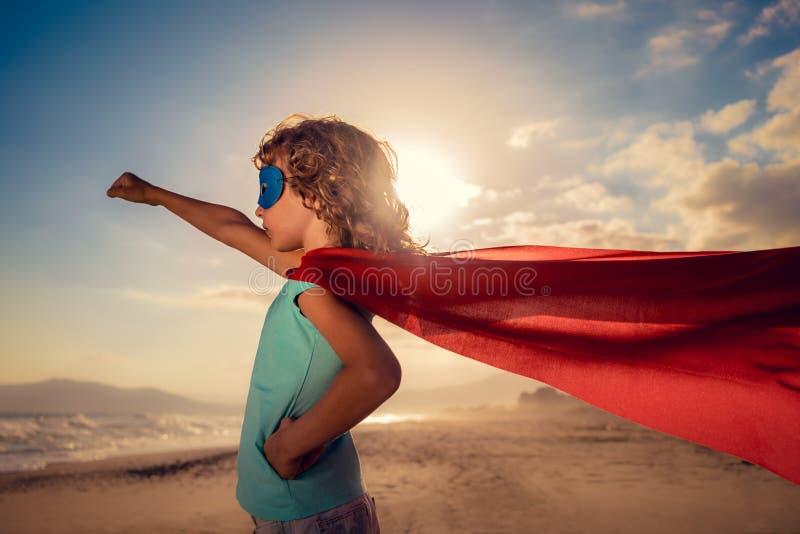 Bambino del supereroe sulla spiaggia Concetto di vacanze estive fotografia stock