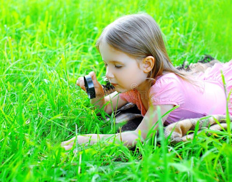 Bambino della bambina che guarda tramite una lente d'ingrandimento fotografie stock libere da diritti