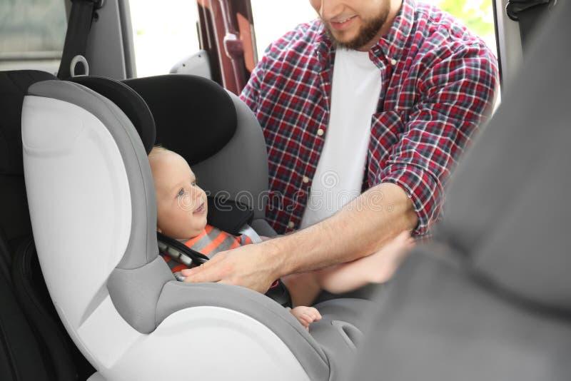 Bambino della legatura del padre al sedile di sicurezza del bambino immagini stock libere da diritti