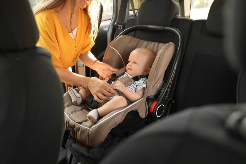 Bambino della legatura della madre al sedile di sicurezza del bambino fotografia stock libera da diritti