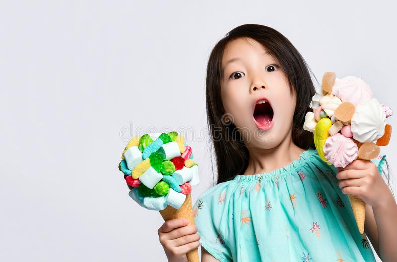 Bambino della neonata che mangia grande gelato dolce due nei coni delle cialde con la marmellata d'arance saporita della caramell fotografia stock