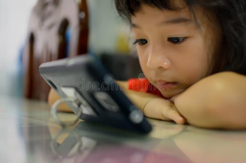Bambino della nuova generazione facendo uso di nuova tecnologia da giocare o guardare immagine stock libera da diritti