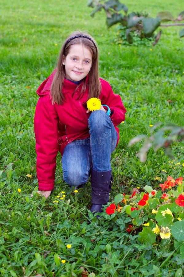 Bambino della ragazza che propone con un fiore in un prato immagine stock