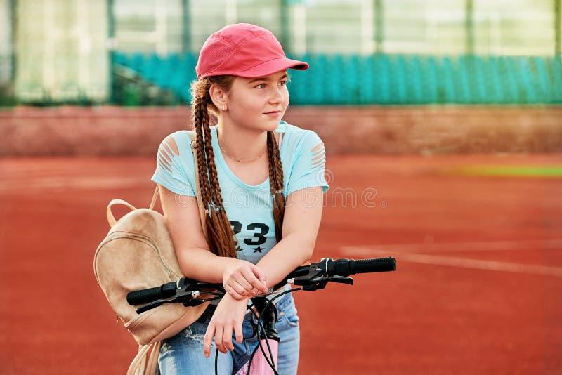 bambino della ragazza che si rilassa sullo stadio Lo stile di vita della ragazza in bici immagini stock libere da diritti