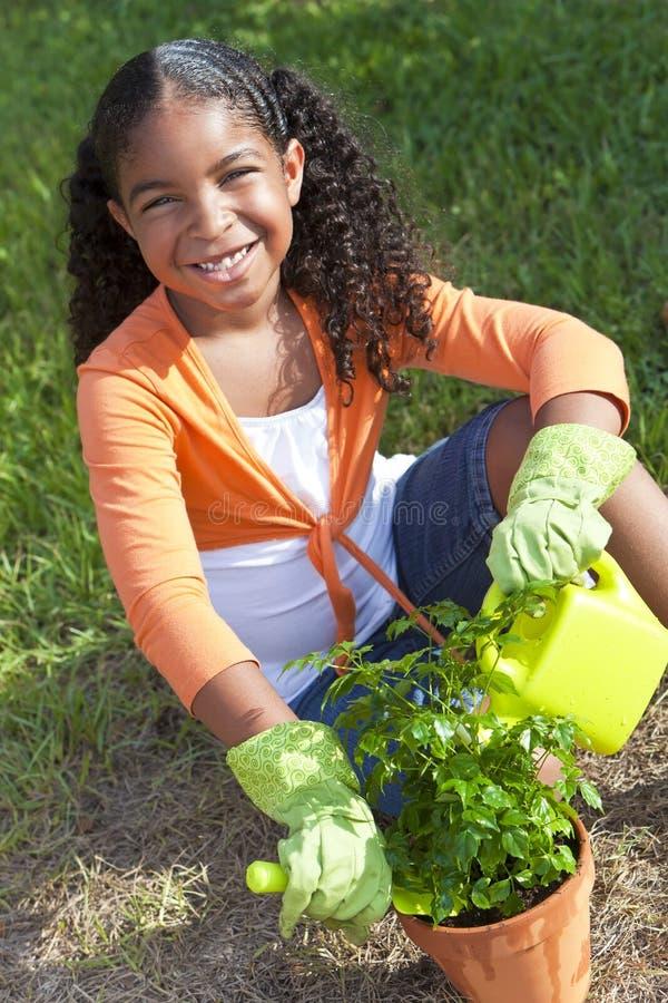 Bambino della ragazza dell'afroamericano che fa il giardinaggio con i fiori immagine stock