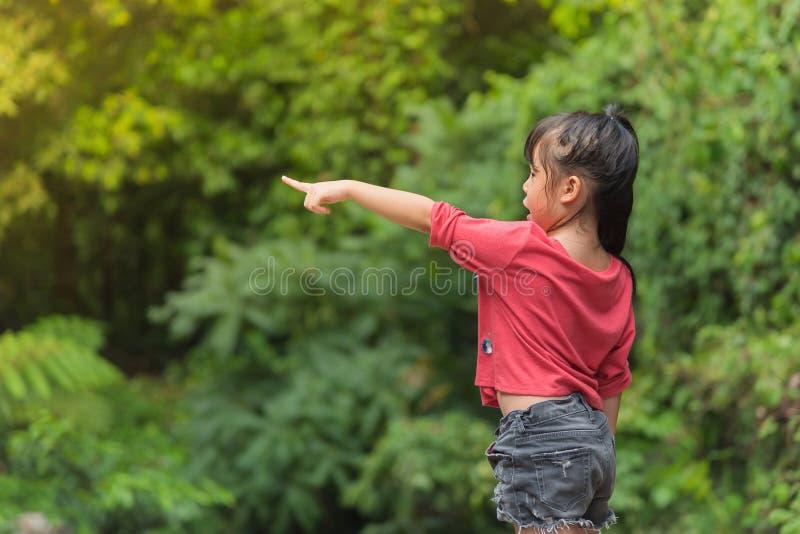 Bambino della ragazza dell'Asia nel dimenamento rosso della maglietta gli alberi immagini stock