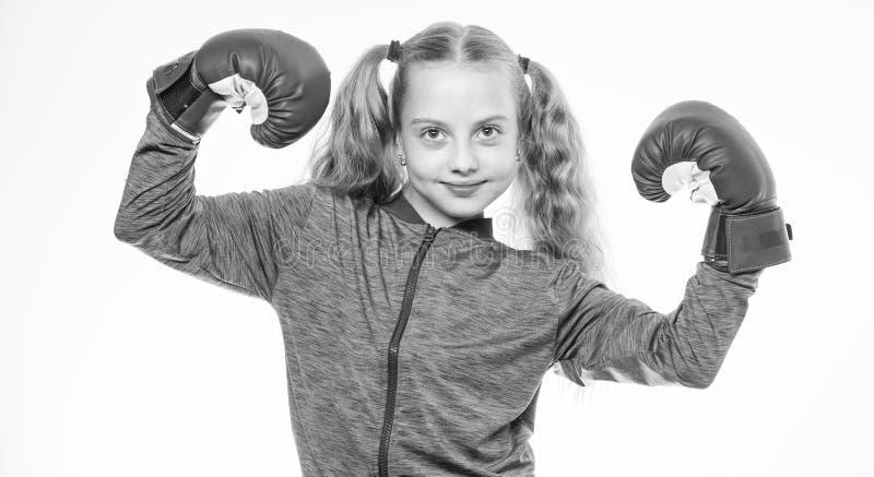 Bambino della ragazza forte con i guantoni da pugile che posano sul fondo bianco Aspetta per difendersi Educazione di sport per l immagine stock