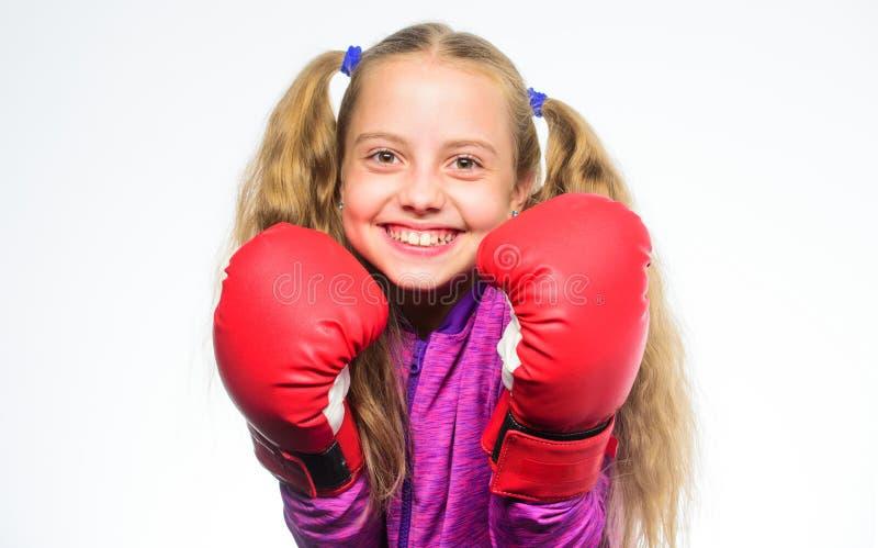 Bambino della ragazza forte con i guantoni da pugile che posano sul fondo bianco Aspetta per difendersi Educazione di sport per l immagini stock libere da diritti
