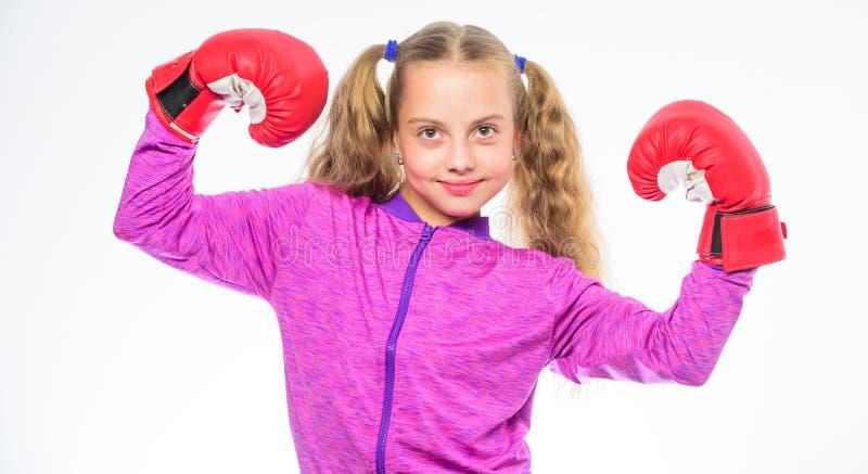 Bambino della ragazza forte con i guantoni da pugile che posano sul fondo bianco Aspetta per difendersi Educazione di sport per l fotografie stock