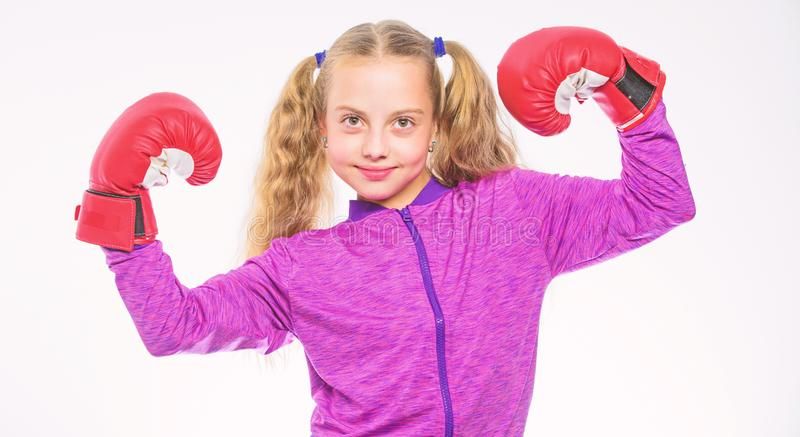 Bambino della ragazza forte con i guantoni da pugile che posano sul fondo bianco Aspetta per difendersi Educazione di sport per l fotografia stock libera da diritti