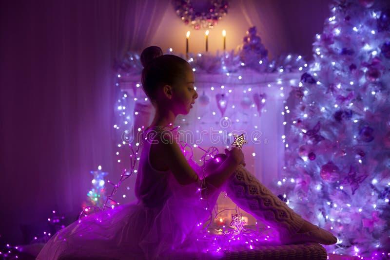 Bambino della ragazza, luci dell'albero di Natale, bambino nella notte di festa fotografia stock