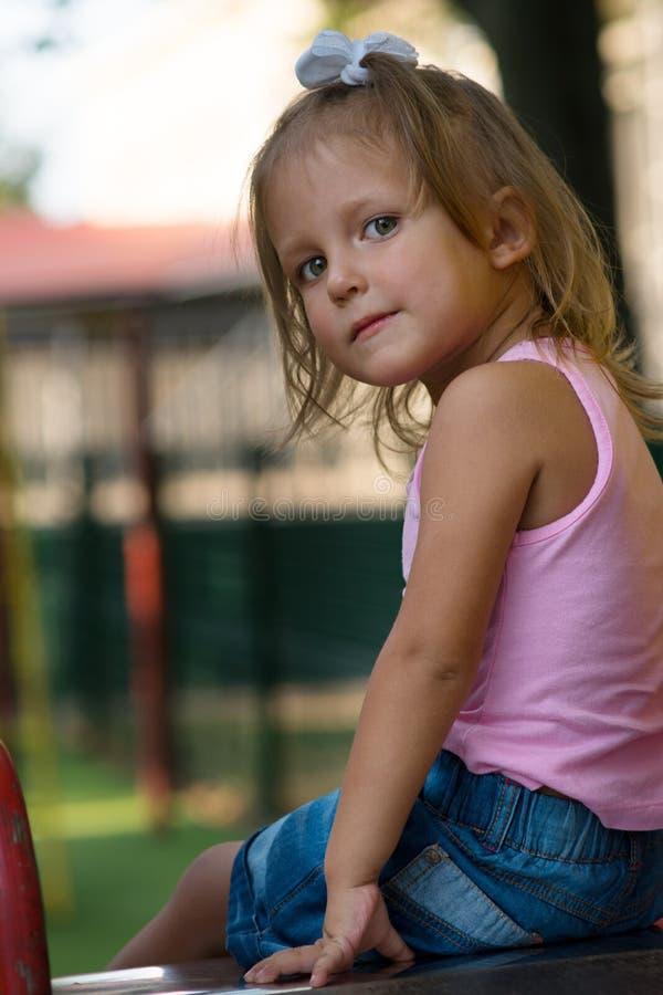 Bambino della ragazza nel campo da giuoco fotografia stock
