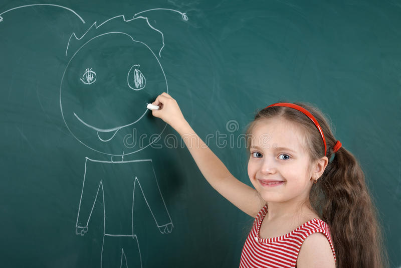 Bambino della scolara in vestito a strisce rosso che disegna uomo felice sul fondo verde della lavagna, concetto di vacanza dei c immagine stock