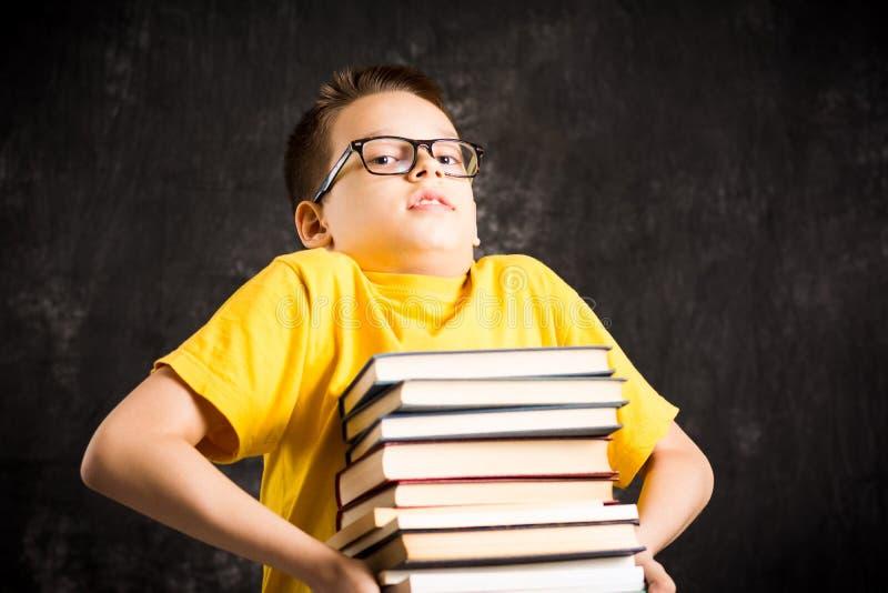 Bambino della scuola che solleva grande mucchio dei libri fotografia stock