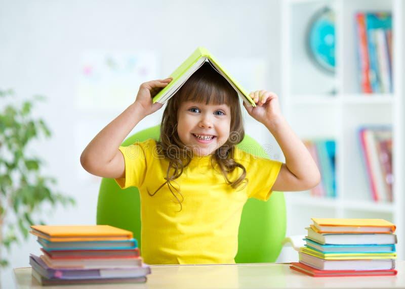 Bambino dello studente con un libro sopra la sua testa immagini stock