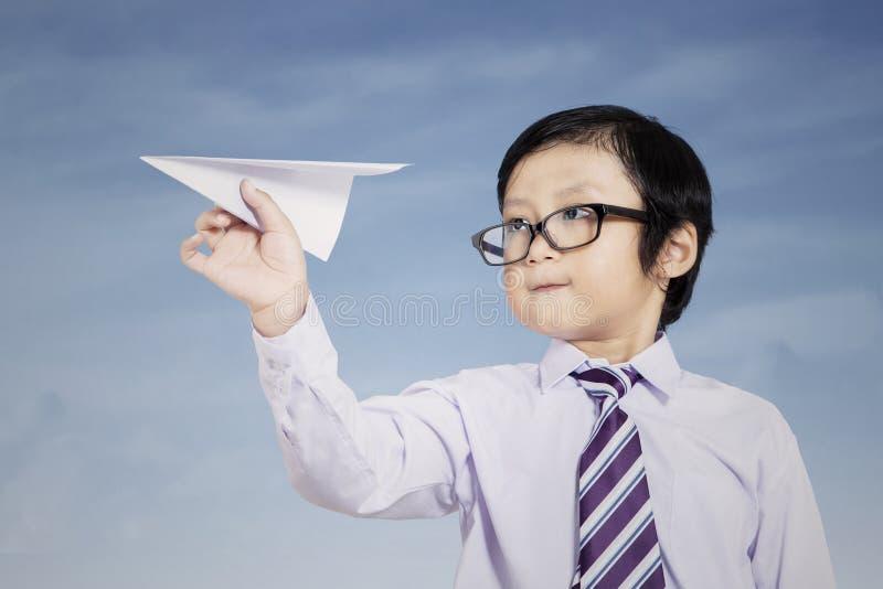 Bambino di affari che giudica aeroplano di carta all'aperto immagine stock