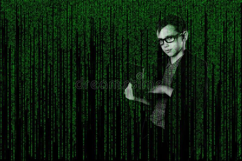 Bambino di affari con dentro un computer portatile del vestito nello stile della matrice pirata informatico su fondo techno-digit immagine stock
