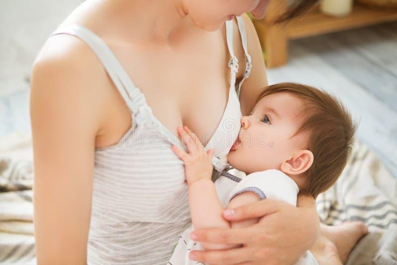 Bambino di allattamento al seno della madre in lei armi a casa Mamma che allatta il suo bambino neonato Bambino che mangia il lat fotografie stock