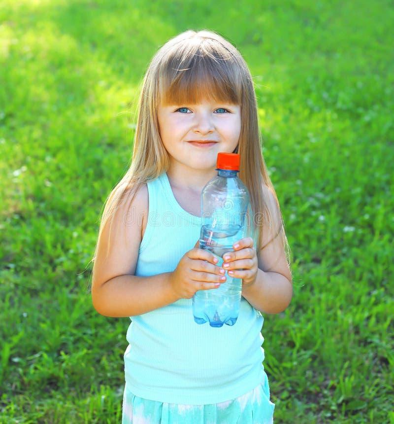 Bambino di Happpy e bottiglia sorridenti della plastica con acqua fotografia stock libera da diritti