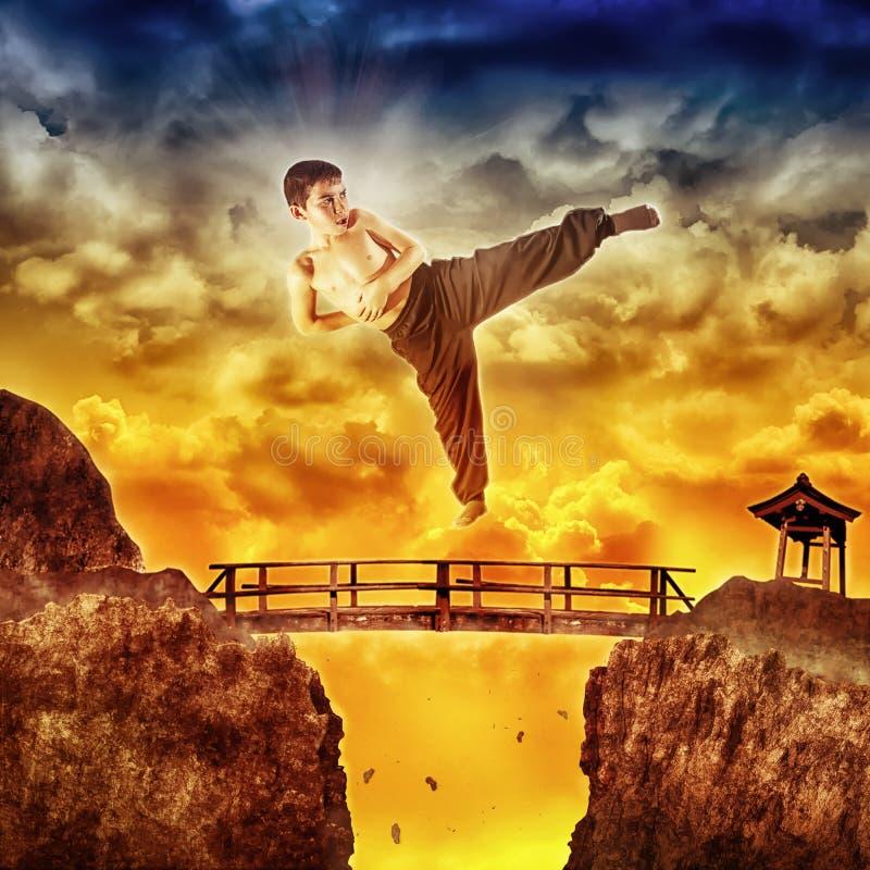 Bambino di karatè che salta sopra il ponte fotografia stock