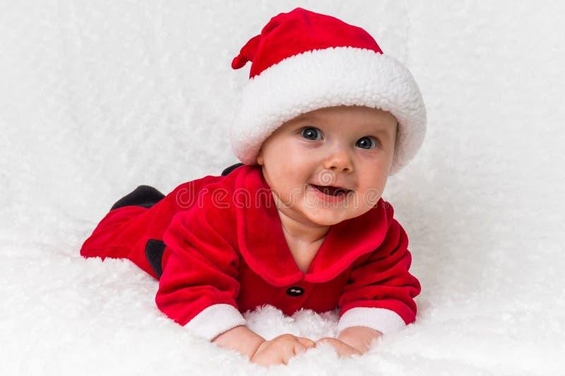 Bambino di Natale in costume di Santa Claus che si trova sulla coperta bianca immagini stock