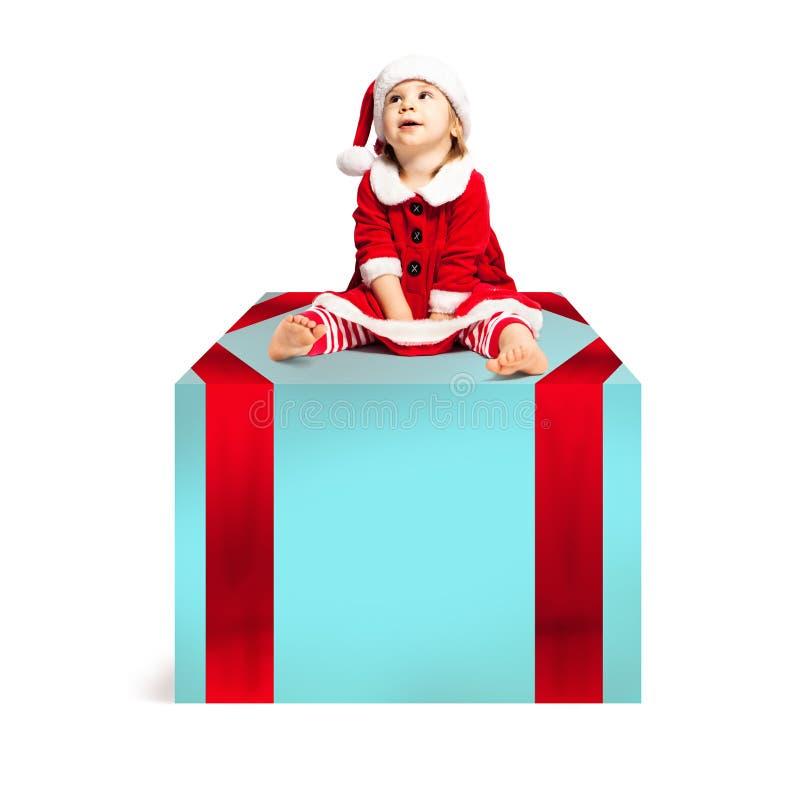 Bambino di Natale in Santa Hat che si siede sul grande contenitore di regalo di natale fotografia stock