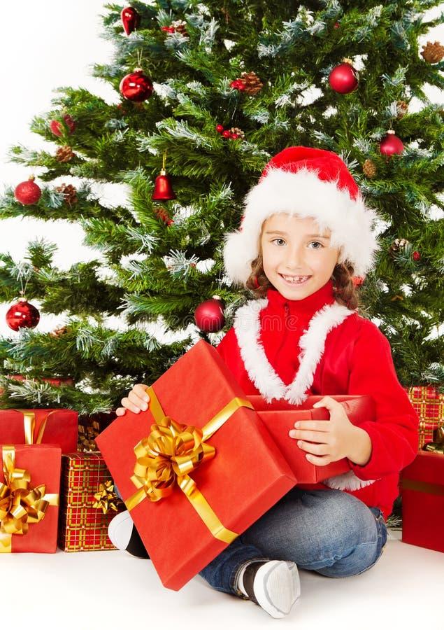 Bambino di Natale sotto il contenitore di regalo attuale d'apertura dell'albero di natale immagine stock