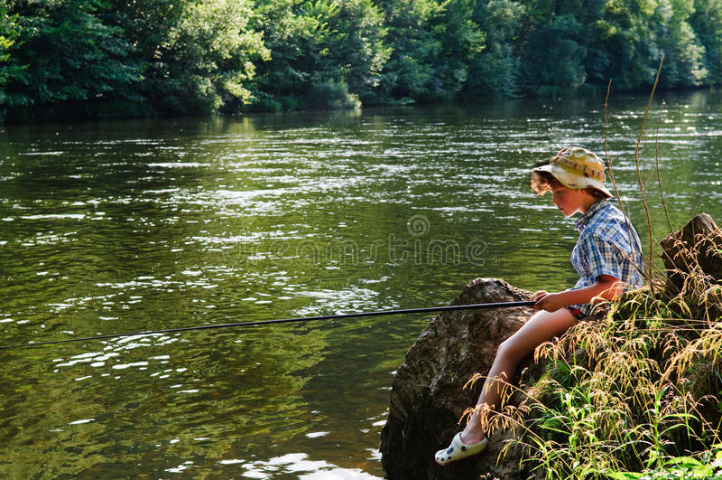 Bambino di pesca con l'amo dal fiume immagine stock