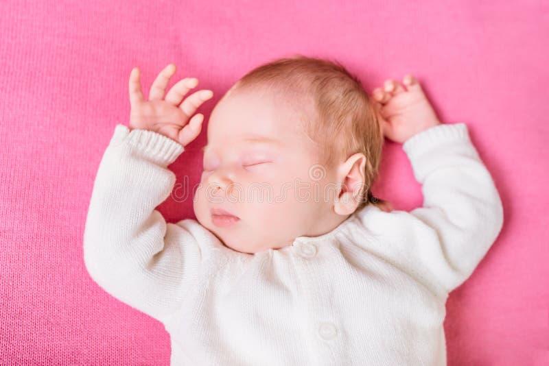 Bambino di 2 settimane con gli occhi chiusi che indossano i vestiti bianchi tricottati immagini stock libere da diritti