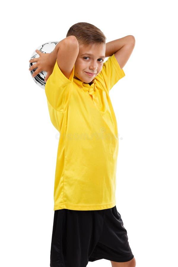Bambino di sport isolato su un fondo bianco Ragazzo sveglio con un pallone da calcio Giovane giocatore di football americano Conc fotografia stock libera da diritti