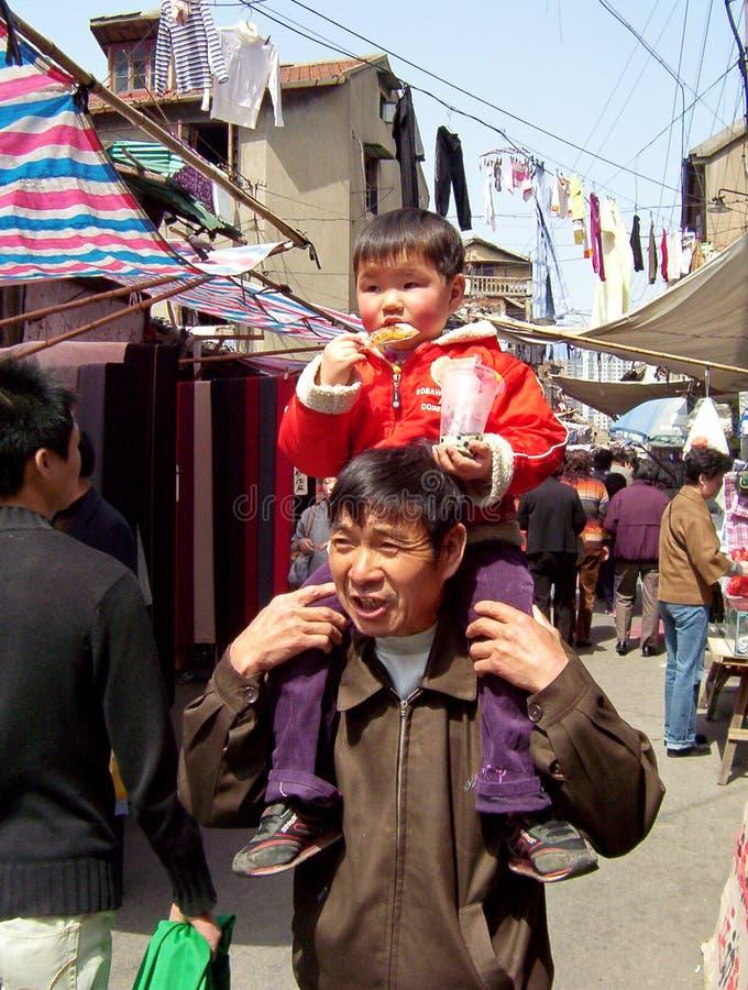 Bambino di trasporto dell'uomo sconosciuto nella vecchia città di Shanghai fotografia stock libera da diritti
