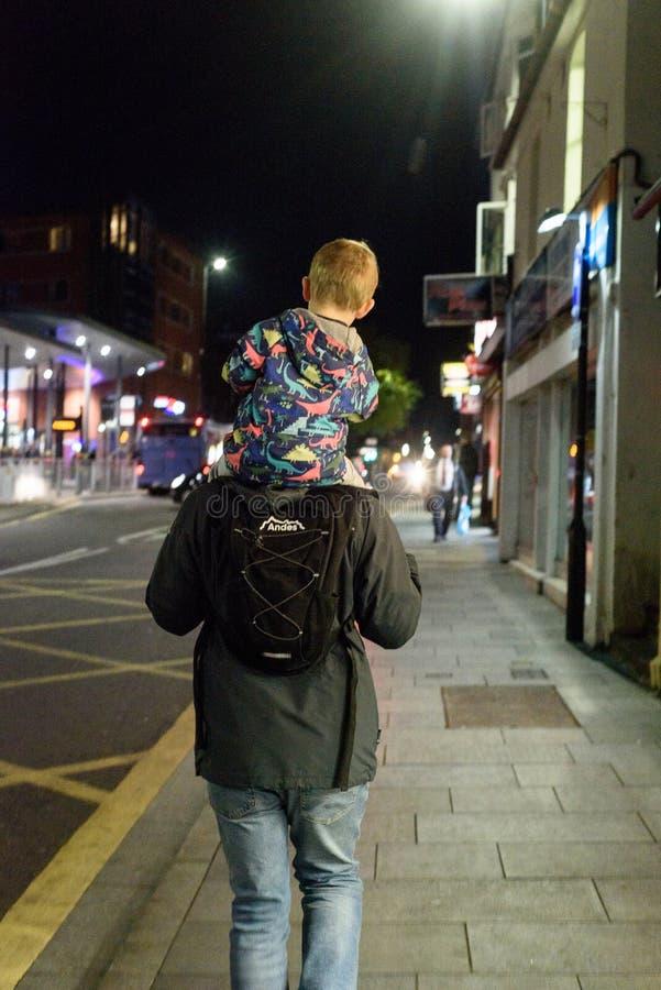 Bambino di trasporto dell'uomo sulle spalle fotografia stock