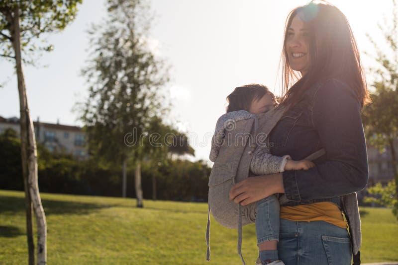 Bambino di trasporto della madre fotografia stock