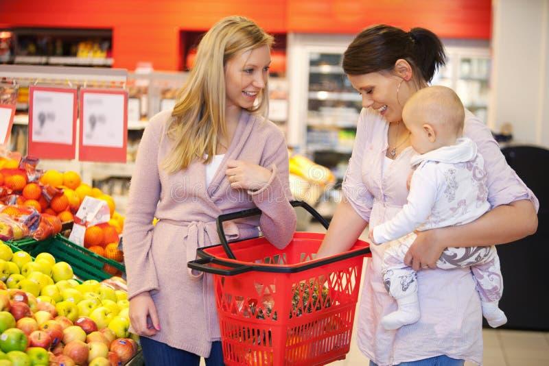 Bambino di trasporto della madre con l'amico mentre acquistando fotografia stock libera da diritti