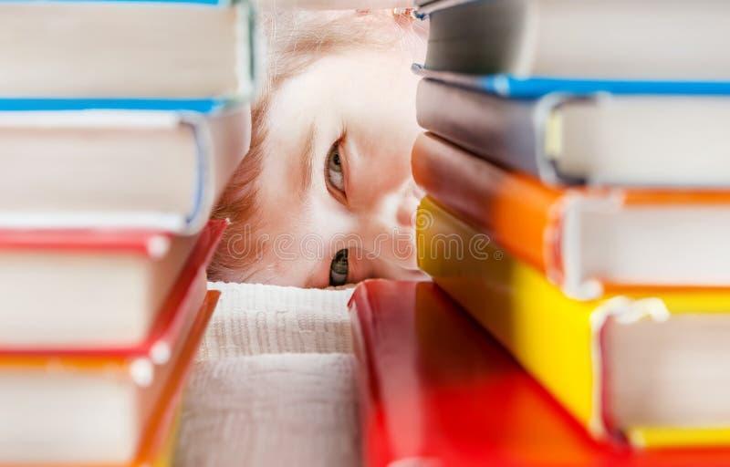 Bambino dietro i libri immagine stock