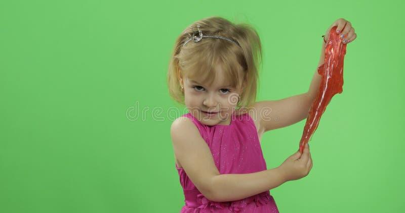 Bambino divertendosi facendo melma rossa Bambino che gioca con la melma fatta a mano del giocattolo fotografie stock libere da diritti