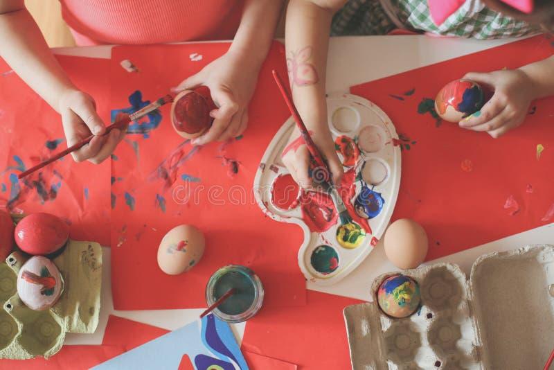 Bambino divertendosi le uova di Pasqua di verniciatura fotografie stock