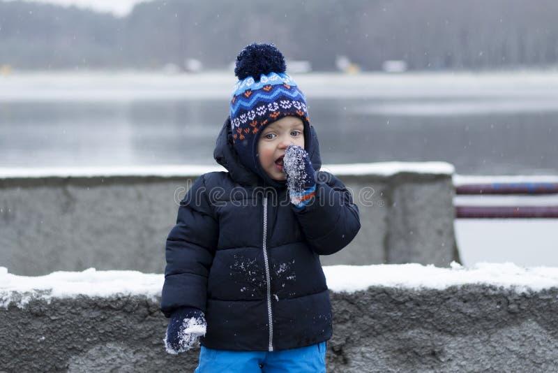 Bambino divertente che mangia neve Sorpreso con un nuovo gusto colpo di inverno fotografie stock